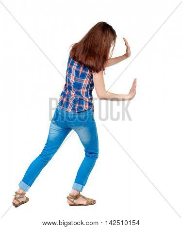 back view of woman pushes wall.  Isolated over white background. Rear view people collection. backside view of person. Girl in plaid shirt shoves something in the side.