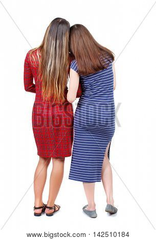 Back view of two young woman. Rear view people collection.  backside view of person. Rear view. Isolated over white background. Two girls in dresses standing close to each other and looking ahead.
