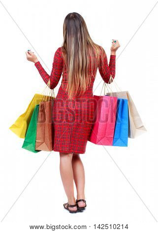 back view of woman with shopping bags. backside view of person.  Rear view people collection. Isolated over white background. The girl in red plaid dress holding multicolored paper bags.