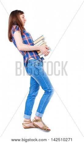 Girl comes with  stack of books. side view. Rear view people collection.  backside view of person.  Isolated over white background. Girl in a plaid shirt goes to the side with a stack of heavy books.