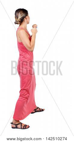 skinny woman funny fights waving his arms and legs. Isolated over white background. A slender woman in a long red dress is standing with clenched fists.