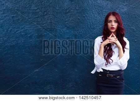 Serious, smart, beautiful, thinking redhead, red-haired girl stand side from big dark blue clean wall holding hands together near the mouth, face and think about something, looking at the camera.