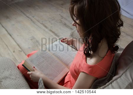 pretty young woman reads a book holding her in his arms