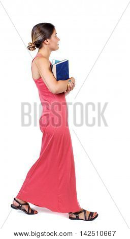 Girl comes with  stack of books. side view. Rear view people collection.  backside view of person.  Isolated over white background. A slender woman in a long red dress goes on the side carrying the