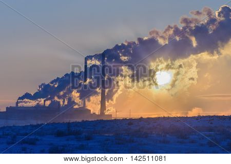 The setting sun makes its way through the dense smoke from the factory chimneys. Polar tundra winter.