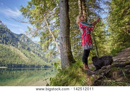 Woman Taking A Selfie Photo Of Lake Vorder Langbathsee In Austria, Salzkammergut In Front Of Mountai