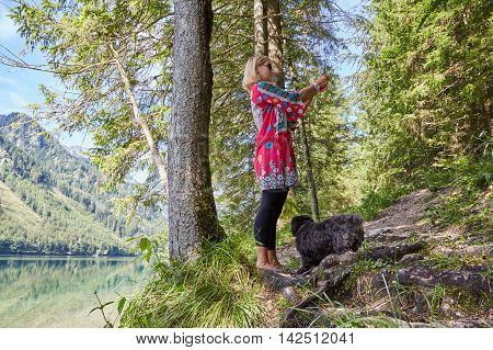 Woman Taking A Selfie Photo In Front Of A Lake