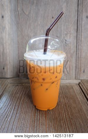 Iced Milk Tea with straw in plastic cup on a wooden table