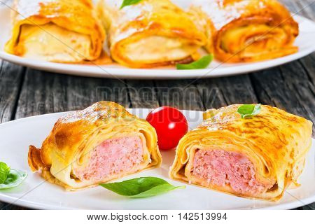 portion of rolled pancakes or crepes stuffed with minced meat and onion on oval dishes served with cherry tomatoes and basil view from above close-up