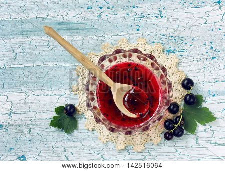 homemade jam blackcurrant with sugar in glass plate on wooden table berries and leaves