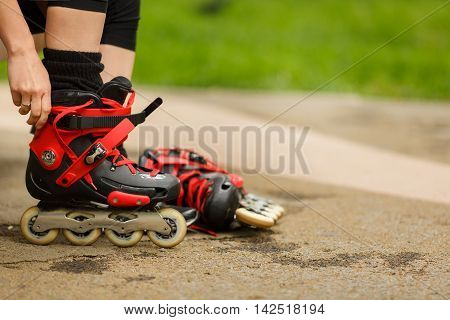 Girl getting ready to ride and wearing red roller blades in park on summer day