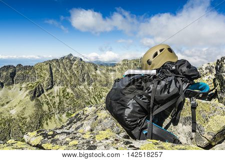 Guide Book, Dark Khaki Helmet And A Black Backpack In The Mountains.