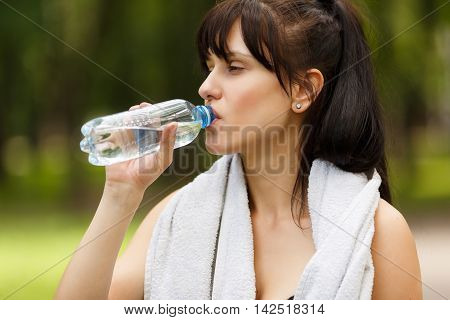 Closeup portrait of sporty brunette girl drinking water outdoors