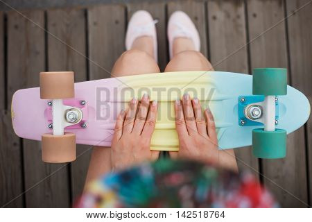 Young girl holding colorful short cruiser penny skate board. Popular small skate deck trendy outfit shot from above focus on hands of model