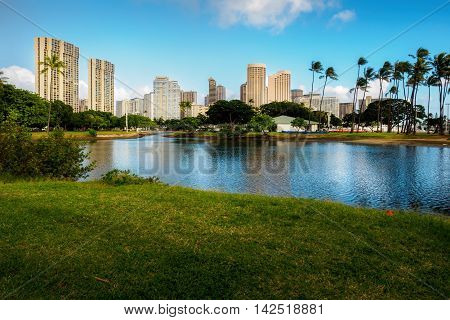 Honolulu, Hawaii, USA - Dec 21, 2015: Ala Moana Park and artificial lake. The background skyscrapers form part of the business district.