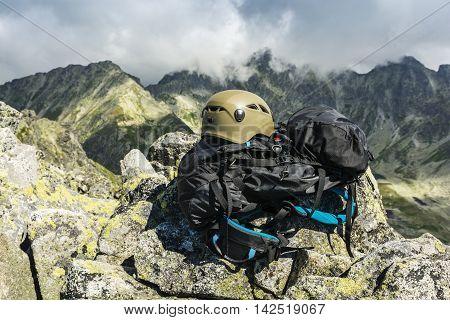 Helmet in color dark khaki and black backpack tourists on the peak.