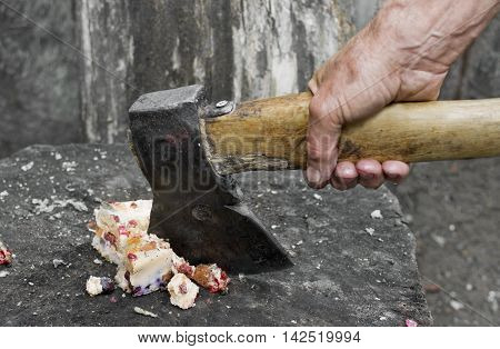 Butcher hand with ax chopping a cheese cake on a butcher block closeup outdoor shot. Concept of quit overeating