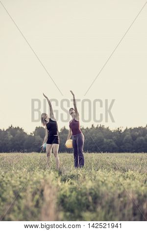 Two fit young women in grassy field exercising while reaching for the sky with copy space.