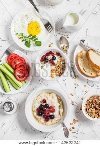 Table breakfast - cottage cheese with yogurt and berries oatmeal with honey and berries fried egg fresh vegetables homemade granola on a light background. Healthy food. Top view