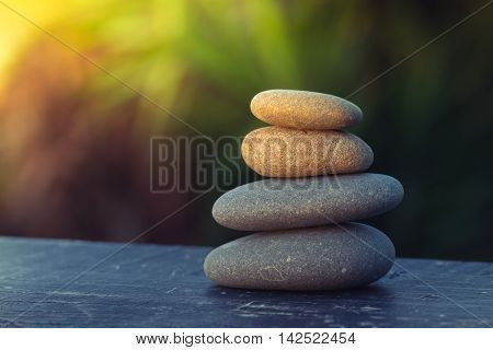 pile of smooth round pebbles balanced on top of an old plank with an out of focus background for copy space and sun flare coming from the top left corner.