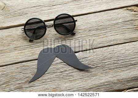 Black Sunglasses And Mustache On A Grey Wooden Table