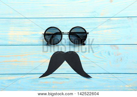 Black Sunglasses And Mustache On A Blue Wooden Table