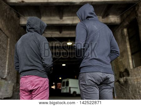 criminal activity, addiction, people and social problem concept - close up of addict men or criminals in hoodies on street