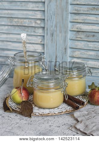 Homemade apple sauce in glass jars on rustic light background