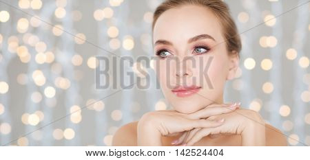 beauty, people and bodycare concept -beautiful young woman face and hands over holidays lights background