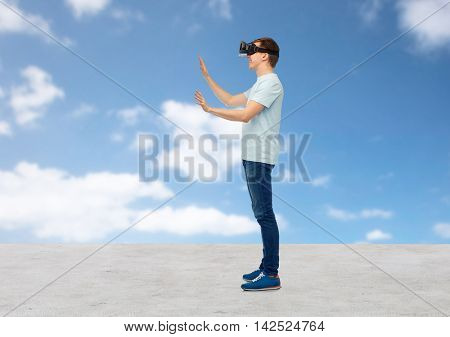 3d technology, virtual reality, entertainment, cyberspace and people concept - man with virtual reality headset or 3d glasses playing game and touching something over blue sky and clouds background