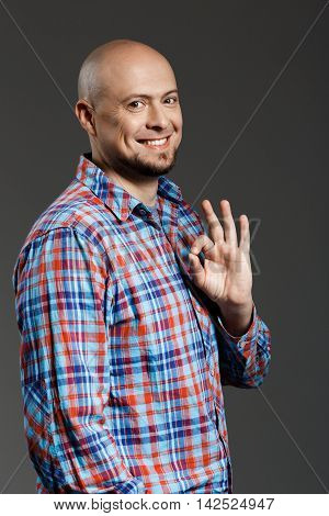 Portrait of confident handsome cheerful middle-aged man in plaid shirt smiling at camera showing ok gesture over grey background. Copy space.