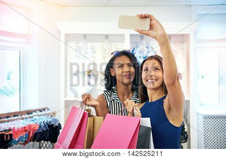 Young attractive female friends taking a selfie in a clothing store as they hold their colorful pink shopping bags filled with purchases