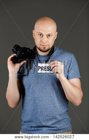 Portrait of handsome middle-aged man in grey shirt with photocamera and press badge posing over dark background. Copy space.
