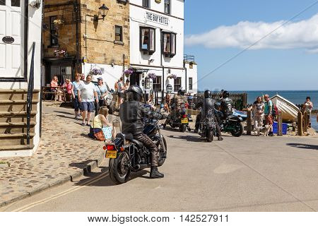 ROBIN HOODS BAY ENGLAND - AUGUST 12: Motorbikers arrive outside The Bay Hotel. In Robin Hoods Bay North Yorkshire England. On 12th August 2016.