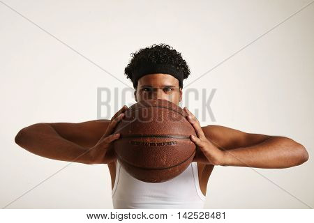 Serious Black Basketball Player With A Ball Next To His Face