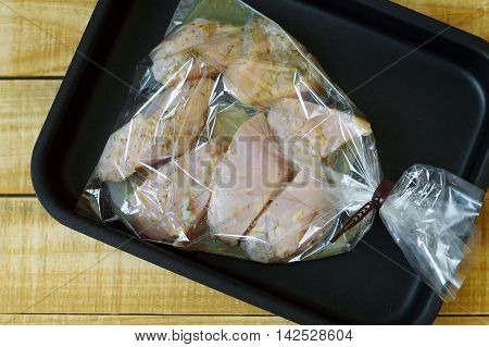 Big chicken slices in a cooking bag. Raw chicken breast flavoured with pepper and herbs on baking tray standing on wooden table