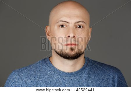 Close up portrait of handsome middle-aged man in grey shirt over dark background. Copy space.