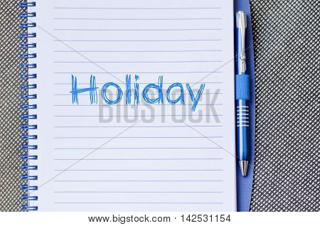 Holiday text concept write on notebook .