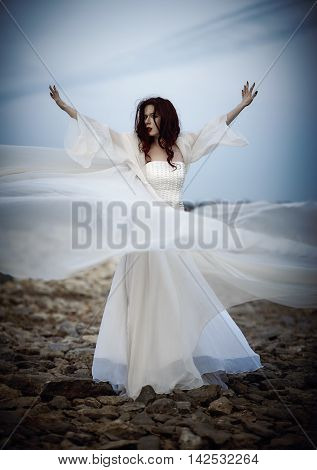 Outdoor portrait of a beautiful sad young woman in white dress