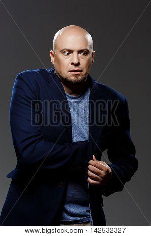 Close up portrait of handsome confident middle-aged businessman over black background. Copy space.