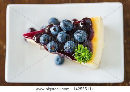 Blueberry cheesecake on white dish closeup topview