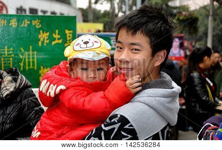 Pengzhou China - March 8 2014: Smiling Chinese youth holding a child at an outdoor marketplace