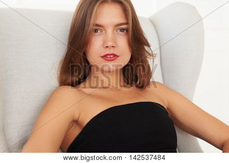 A stunning sharp look of a marvelous young woman, who wears red lips and black dresses