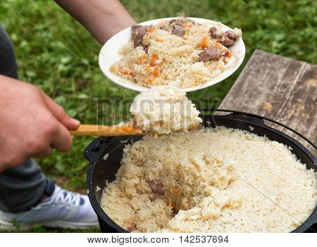 Cook puts pilaf out of the cauldron at the plate outdoors