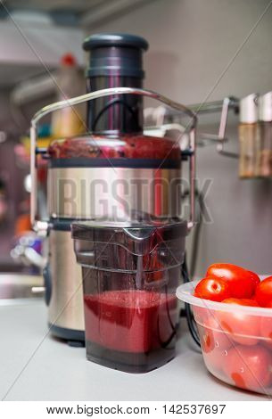 Squeezing tomato juice at home. Juicer in the kitchen. Focus on the foreground