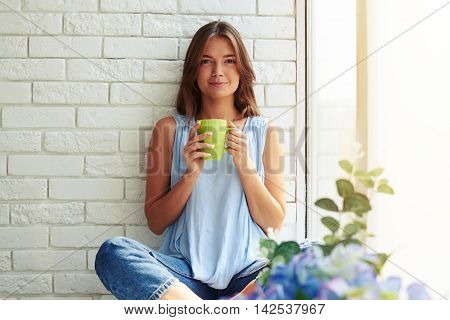 Close-up portrait of pensive delighted young girl sitting on the window-sill and holding a cup of aromatic coffee