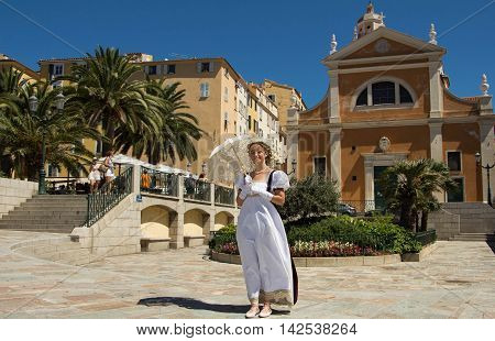 Ajaccio Corsica island France-August 14 2016: The young beautiful lady with umbrella dressed as in Napoleon's time with Our Lady of the Assumption cathedral in the background.