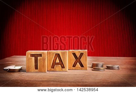 Word tax on wooden blocks with stacked coins. Financial concept.