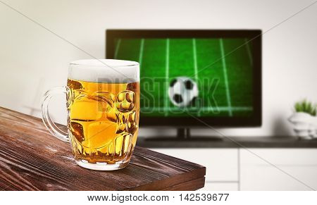 Glass of beer on wooden table in front of television show of football. Watching football match at home.