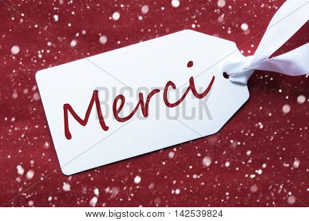 One White Label On A Red Textured Background. Tag With Ribbon And Snowflakes. French Text Merci Means Thank You